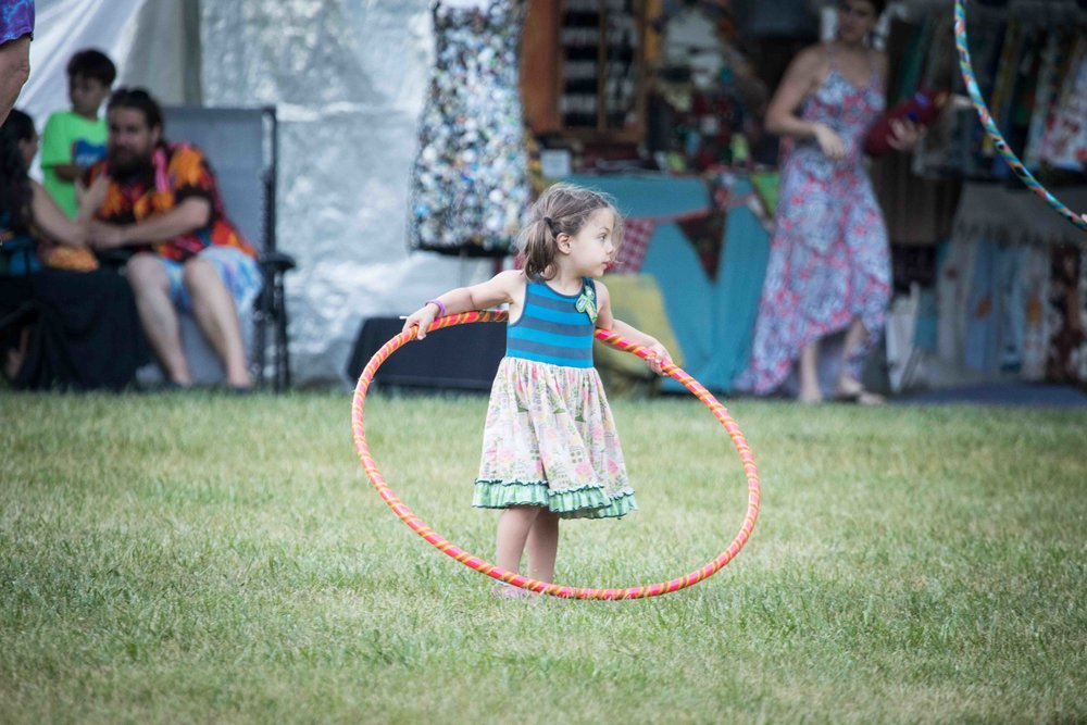 A little girl prepares to attempt the hula hoop