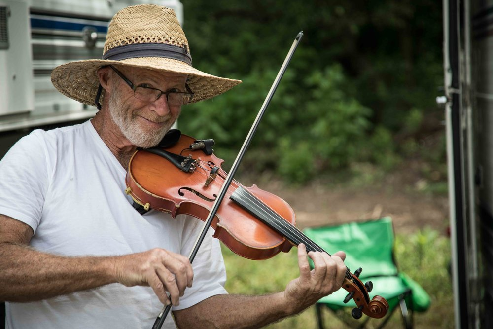 Festival goers bring their own instruments to jam with their tent neighbors