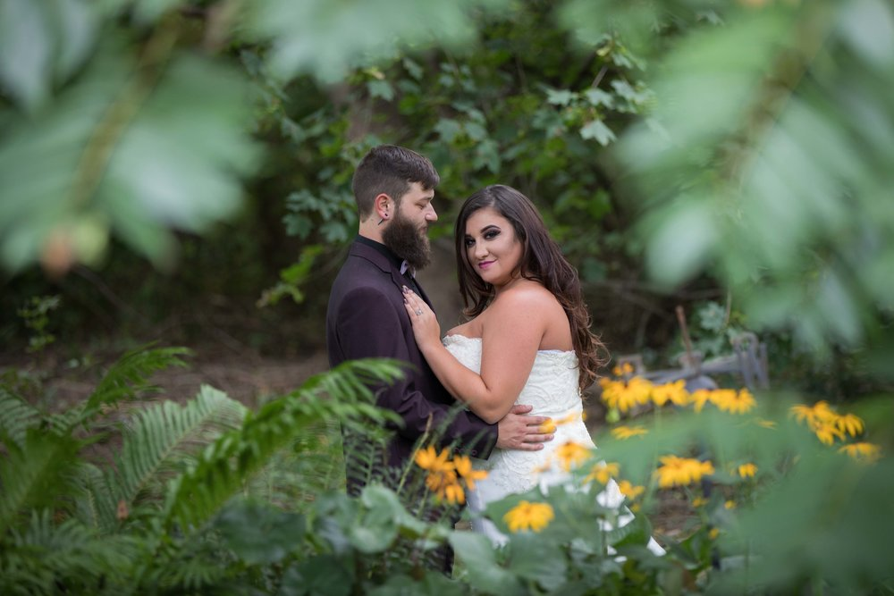 bride and groom pose for portrait through trees.jpg