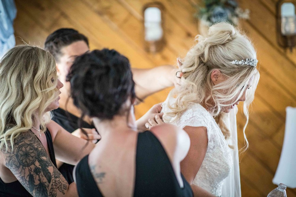 The bridesmaids frantically work together to get the bride in her dress