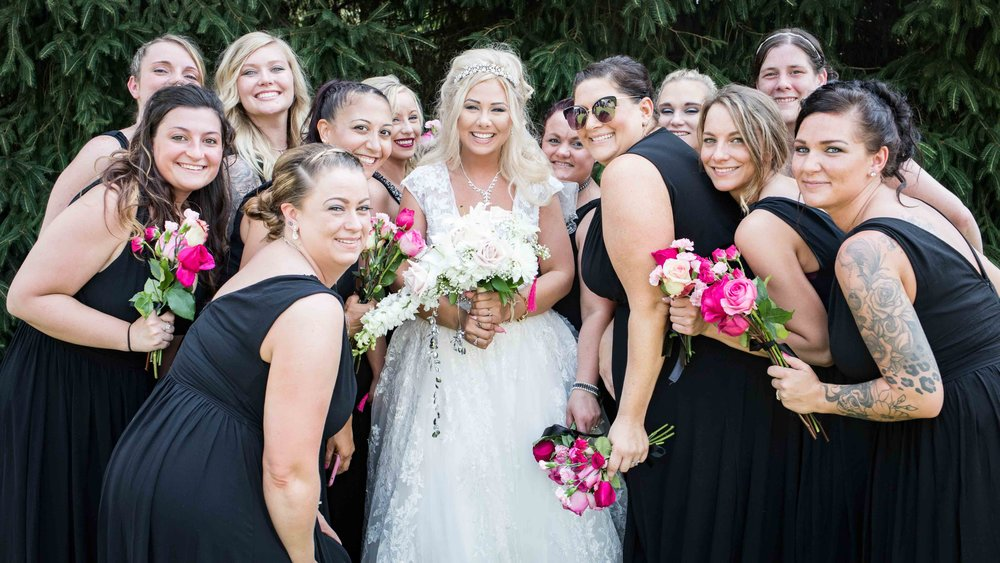 All the bridesmaids bunch together with their flowers for a picture with the bride
