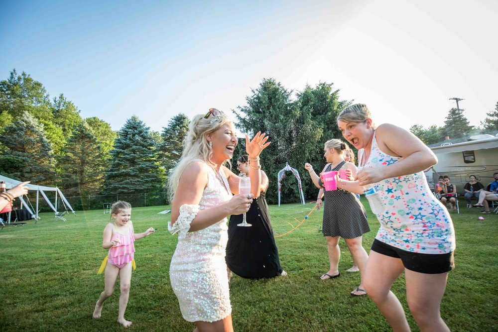 bride and friends dance in the water