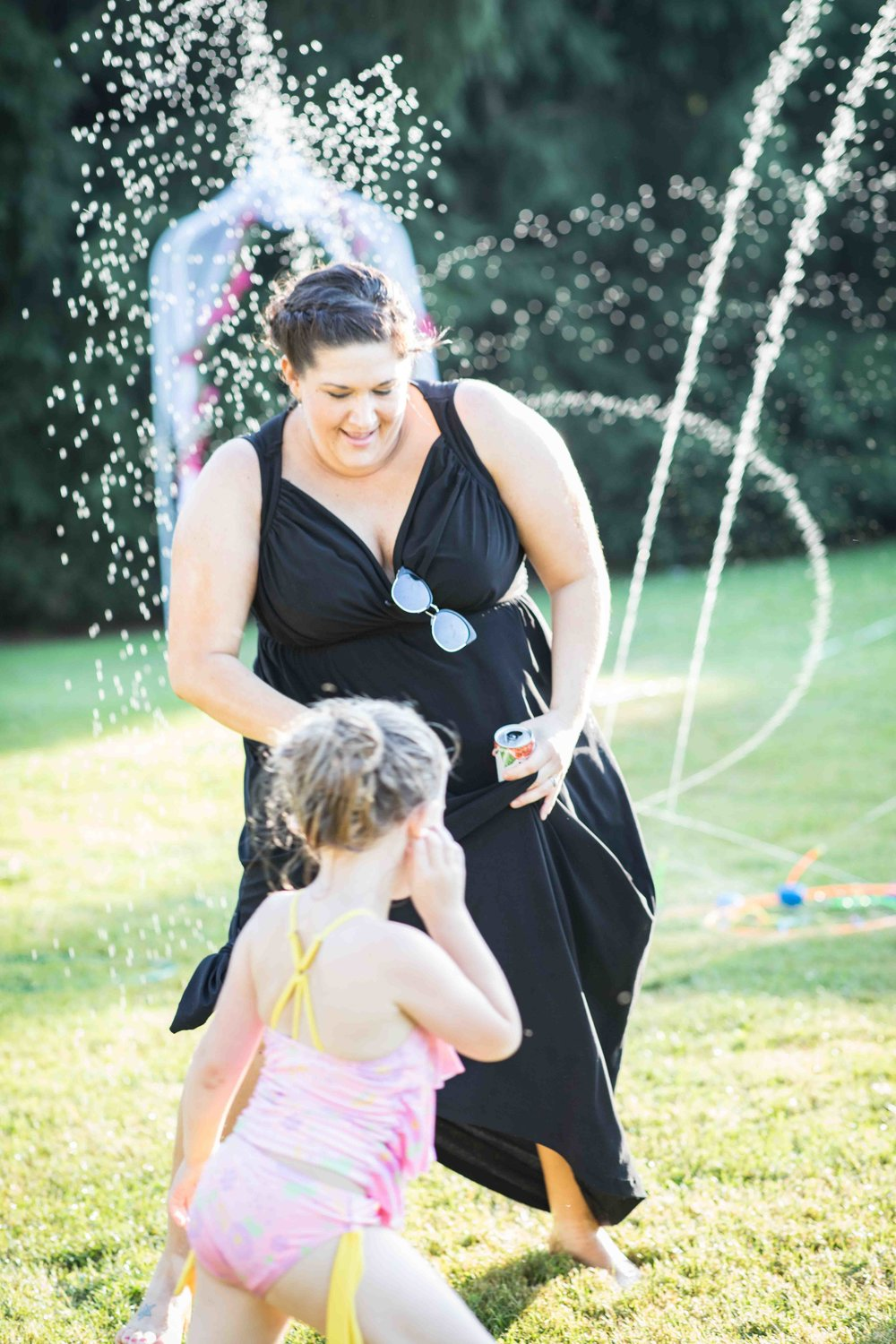 a bridesmaid gets soaked dancing with a little girl in the water