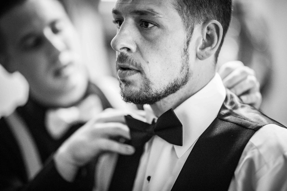 Groomsmen straitens the grooms bowtie as he looks in the mirror