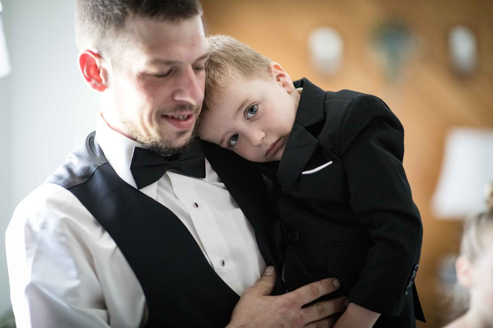 Groom holds the shy ring bearer