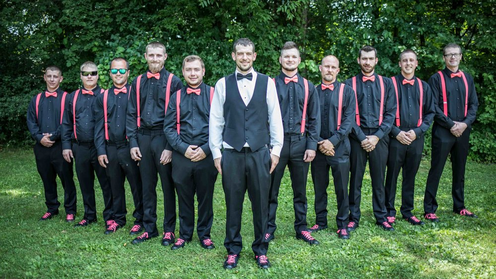 Groom stands up front and center as the 10 other groomsmen wearing black with pink suspenders and bowtie, stand in a v-shape behind him