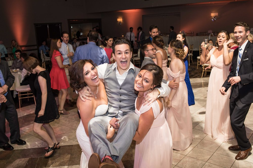 Bride and bridesmaid holding groom on the dance floor all laughing