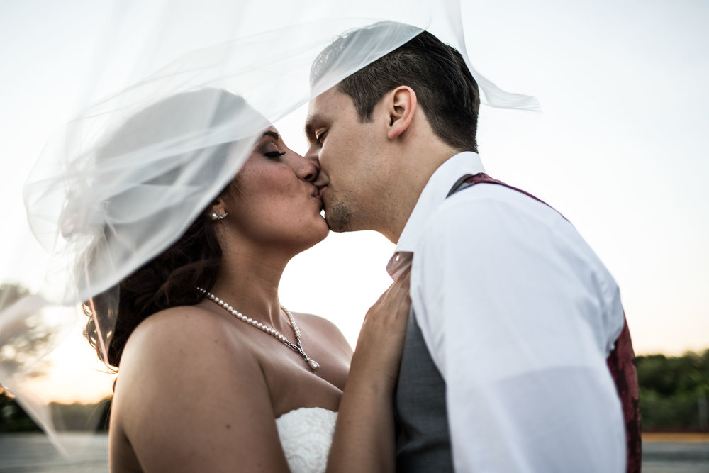 bride and groom kissing through wind blown veil