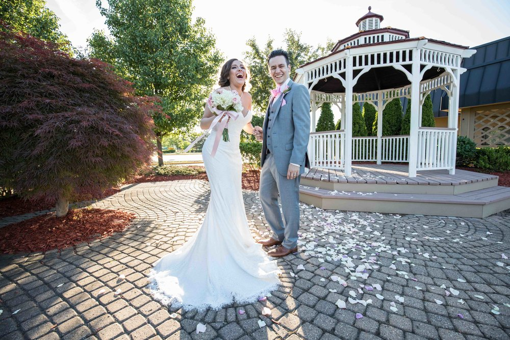 Bride and groom laughing during sunset portraits in front of gazebo