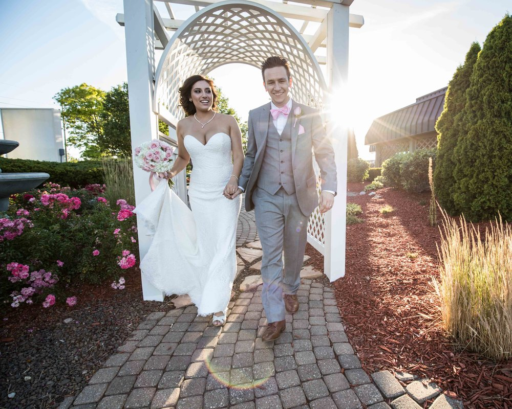 bride and groom walking through a trellis
