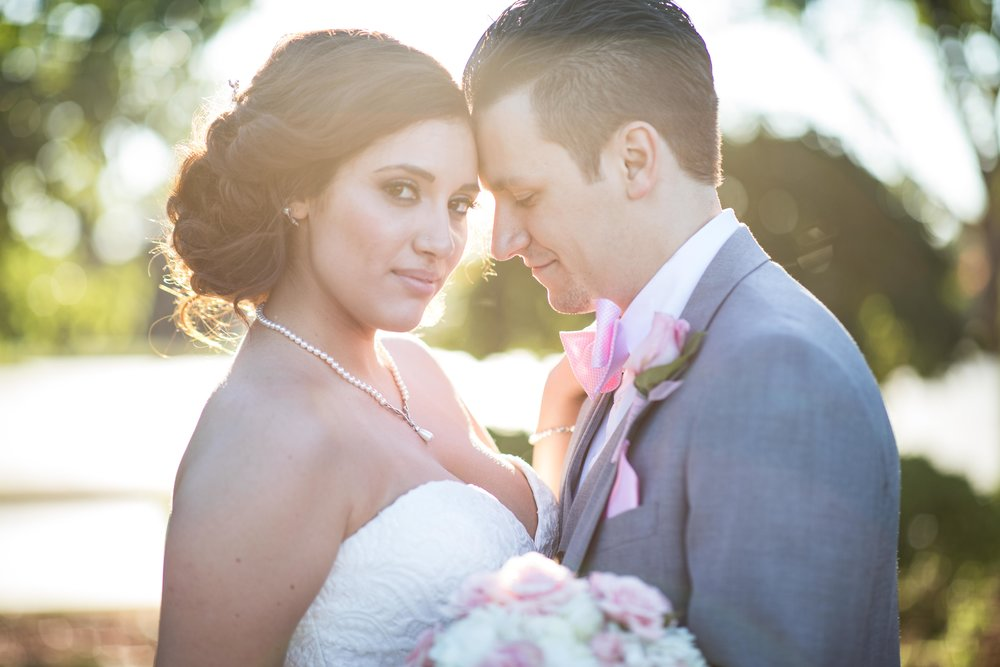 Bride looks directly at the photographer while the groom holds her close during sunset
