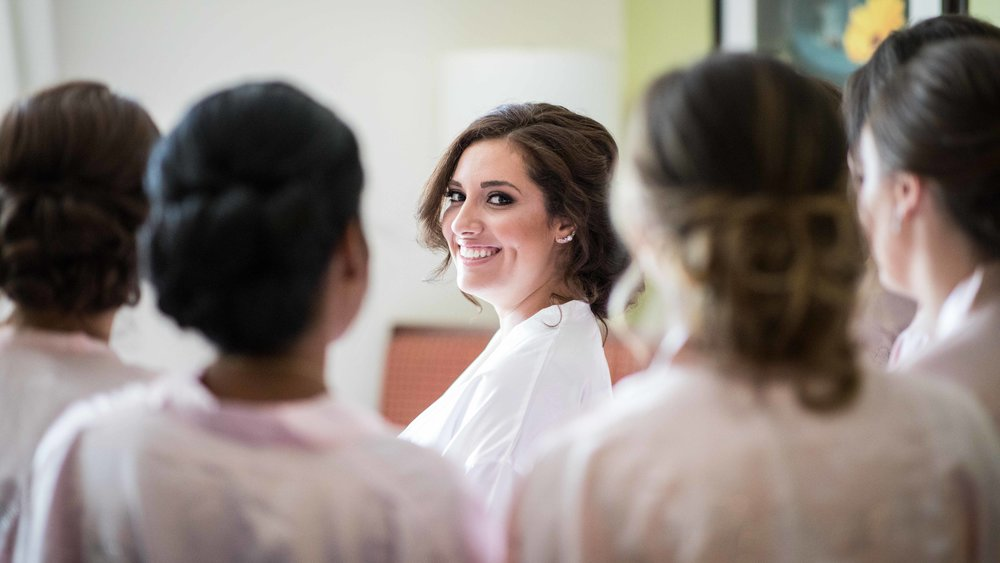 bride smiling through a circle of her bridesmaids.jpg