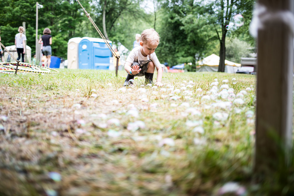 a small child popping bubbles which are scattered all over the ground in front of him