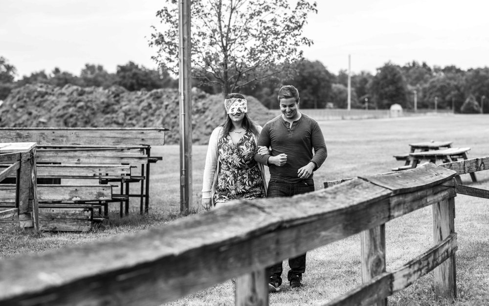 A man leading his blindfolded girlfriend along a split rail fence