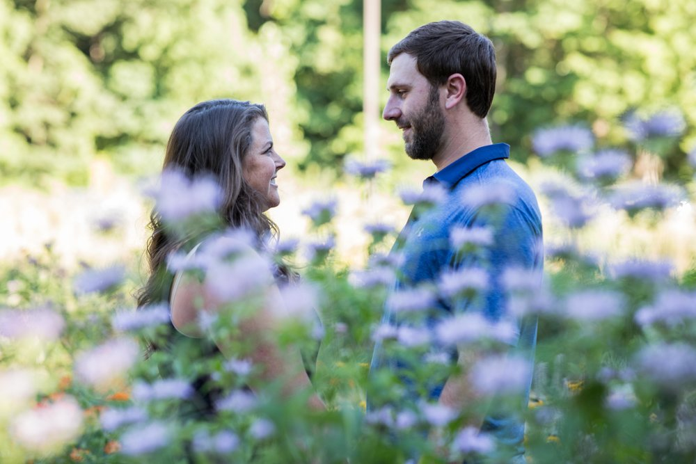 A man and woman hold hands in front of a field of wildflowers