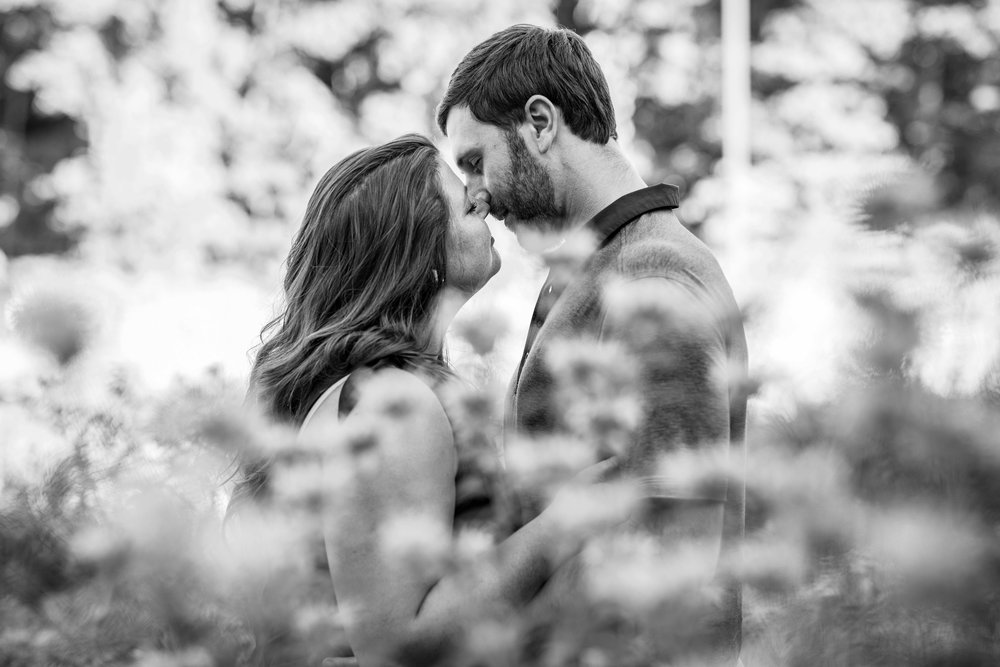 black and white image of a woman kissing her fiancé with wildflowers all around