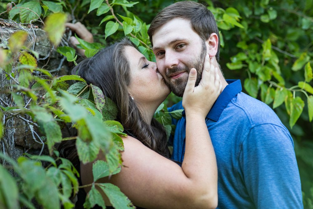 woman kisses a mans cheek as he looks into the camera, they're both leaning against a stone wall covered in ivy