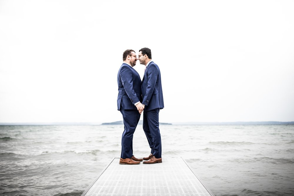 a couple holds each other at the end of a dock in front of the Grand Travers Bay