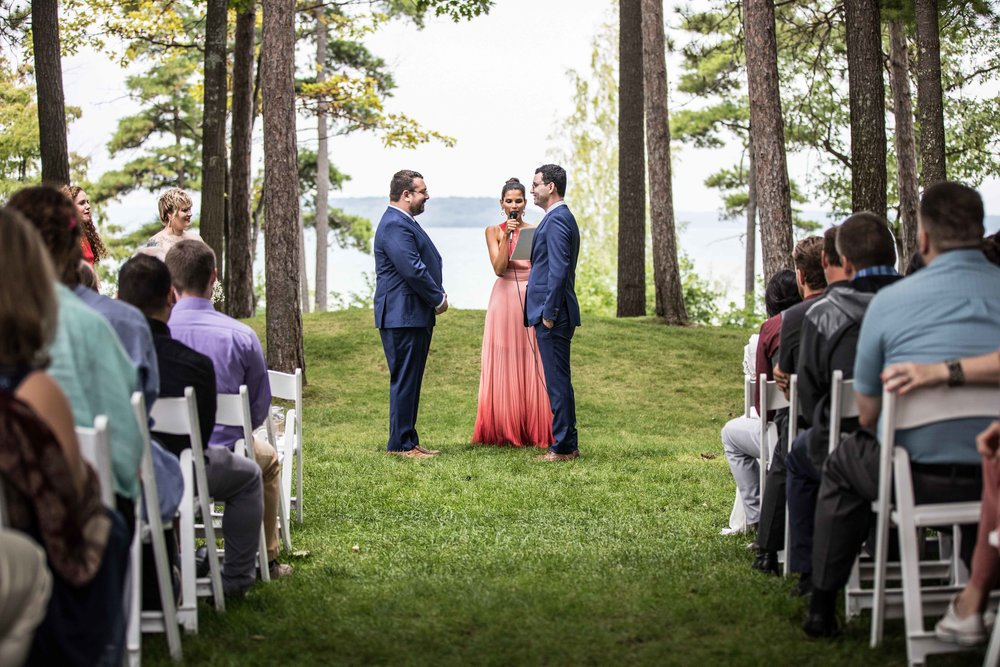 A wedding ceremony for two grooms in front of the Grand Traverse Bay of Lake Michigan