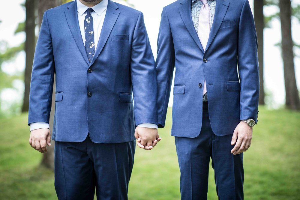 The two grooms hold hands during the ceremony