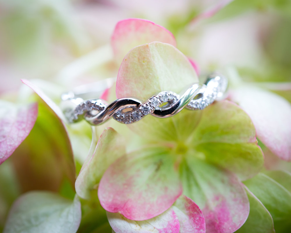 close up photo of wedding band set on a flower, showing diamonds and detail