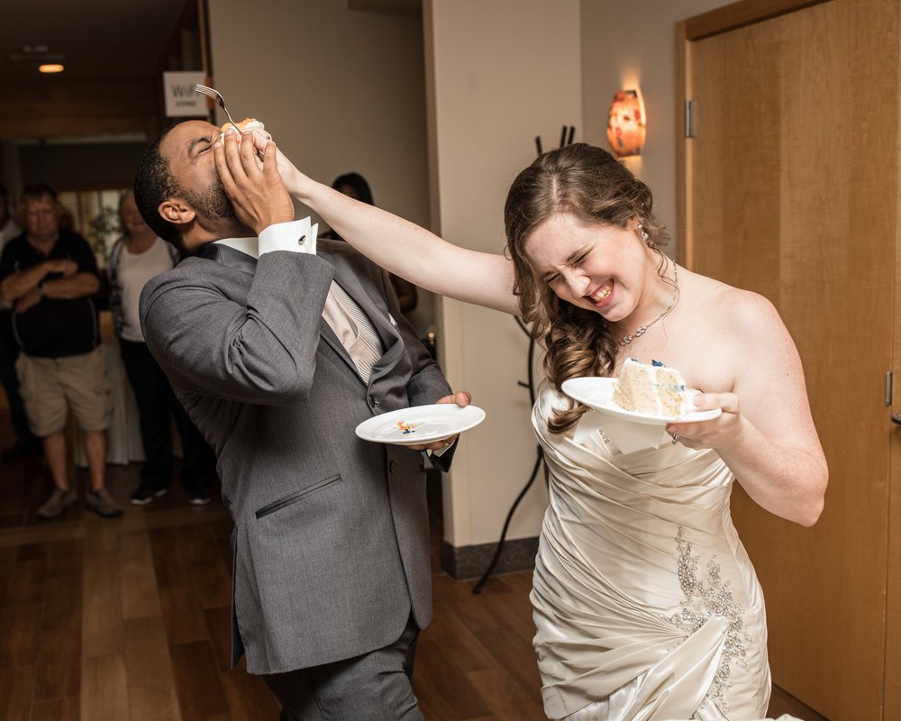 the bride smashes cake in the groom's face during cake cutting