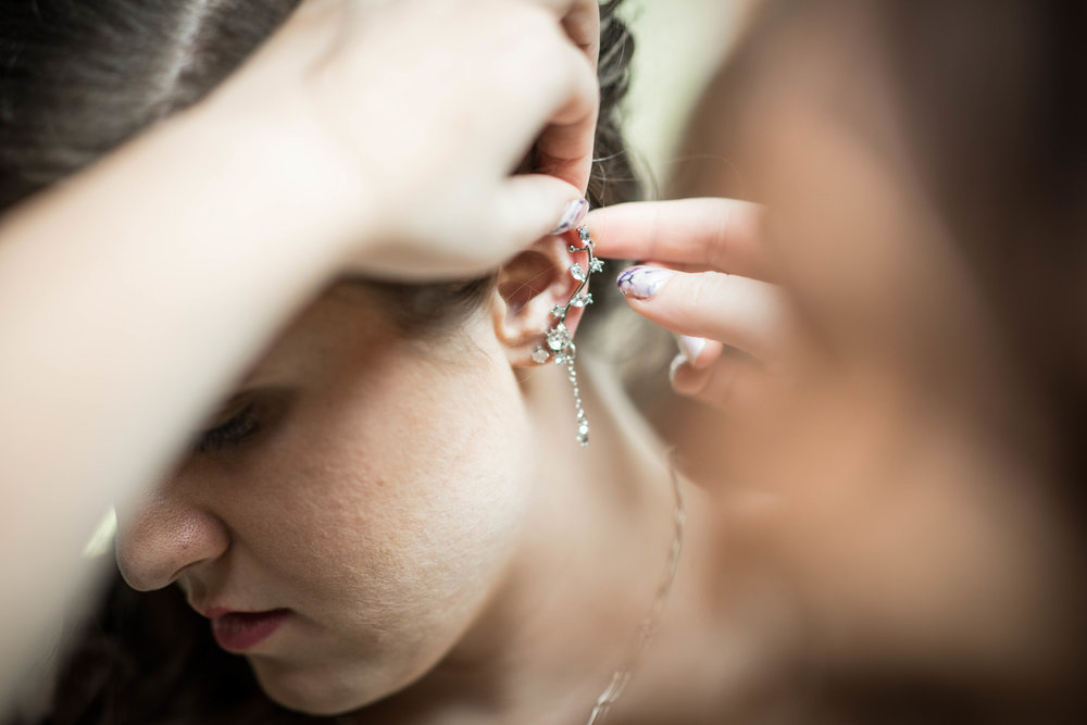 close up of the bride getting help with earrings from her maid of honor