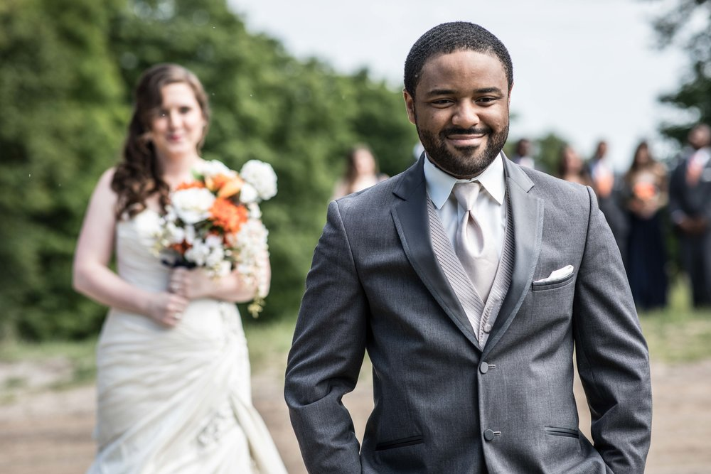 The bride walks up behind the groom as he smiles in anticipation for the first look