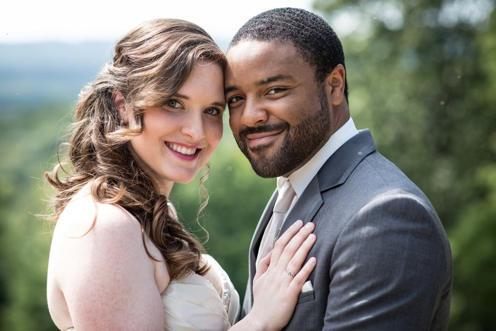 Close up of bride and groom holding each other with a mountainous background