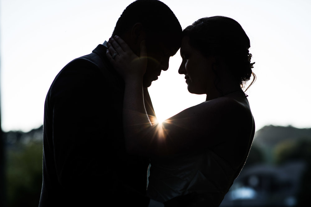 dramatic silhouette of bride and groom holding each other as the setting sun shines through between them