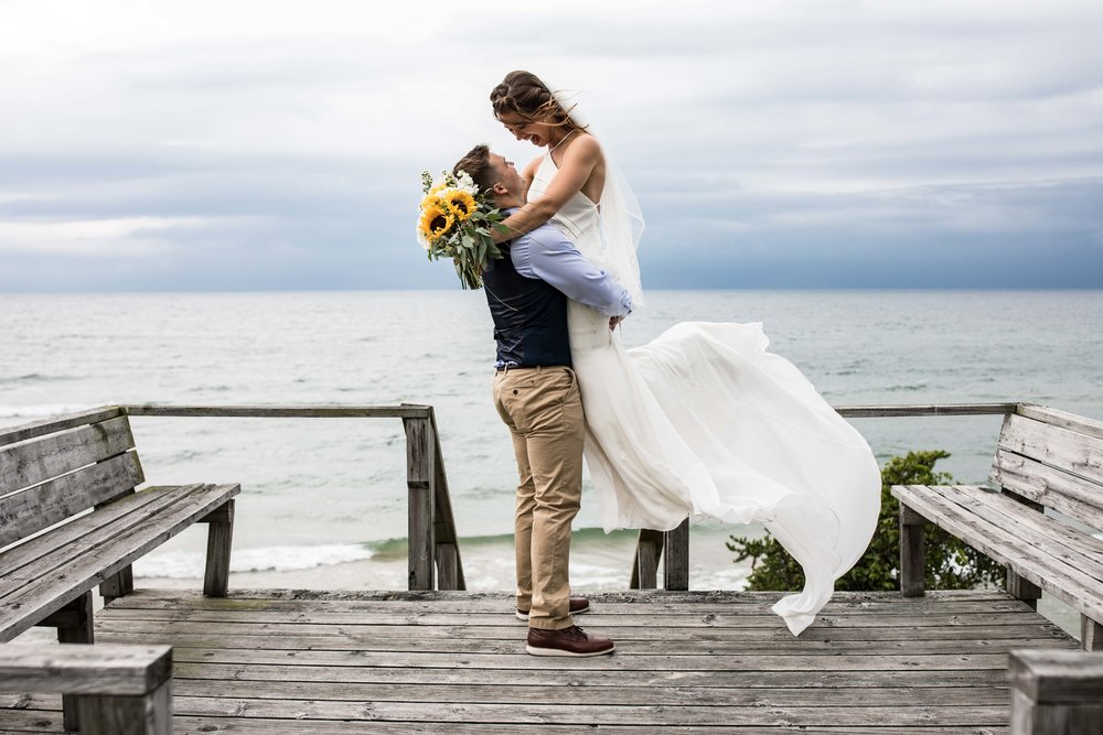 the groom lifts the bride up into the air standing at an overlook to Lake Michigan as her white dress blows in the wind