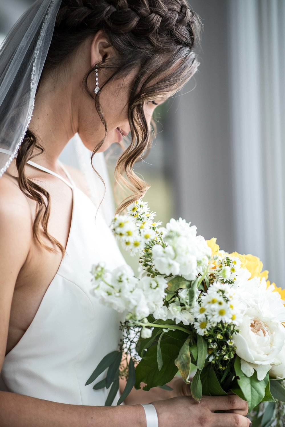 bride looks down into her flower bouquet