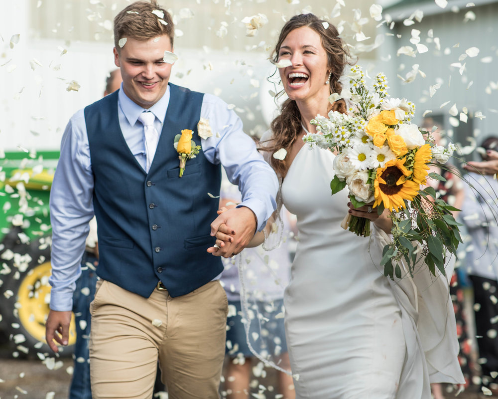 flower pedals are thrown at the bride and groom as they exit for their honeymoon