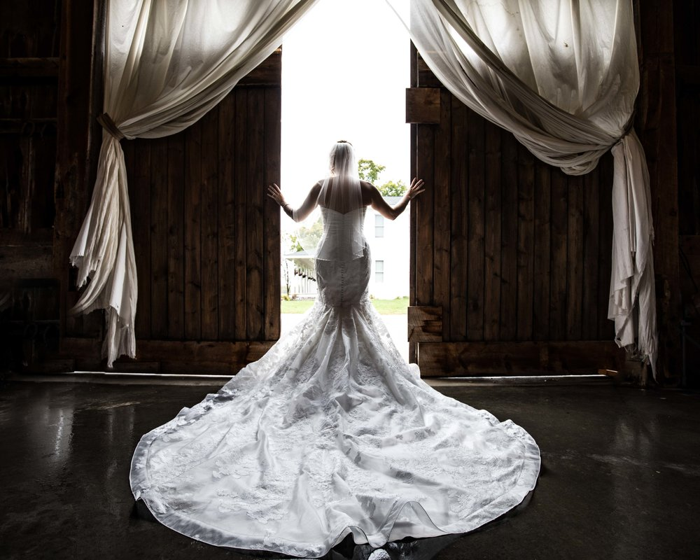 Bride in a white dress with the train spread out as she pushes open the barn doors