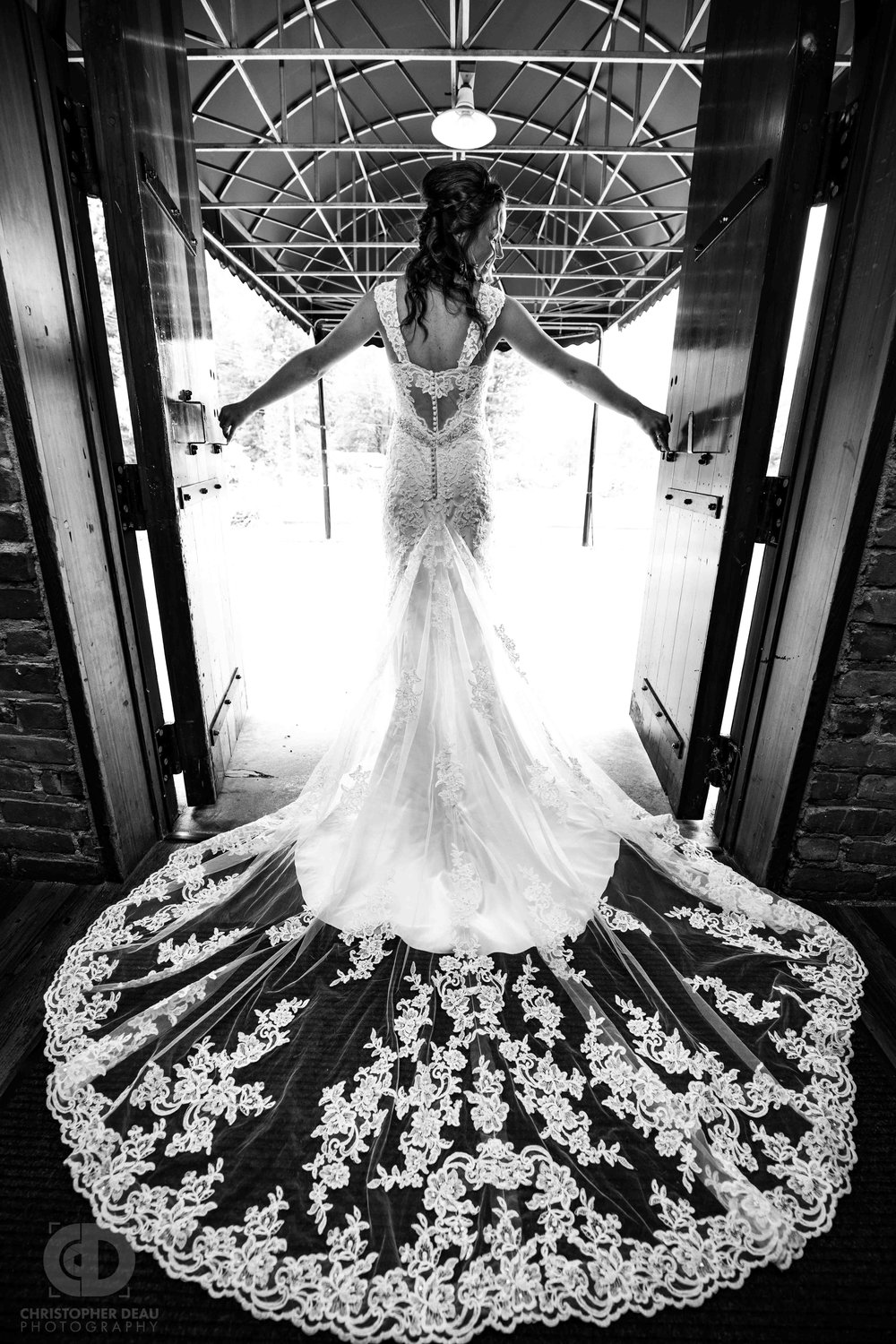 Stunning bride in flowing white lace dress standing in door way