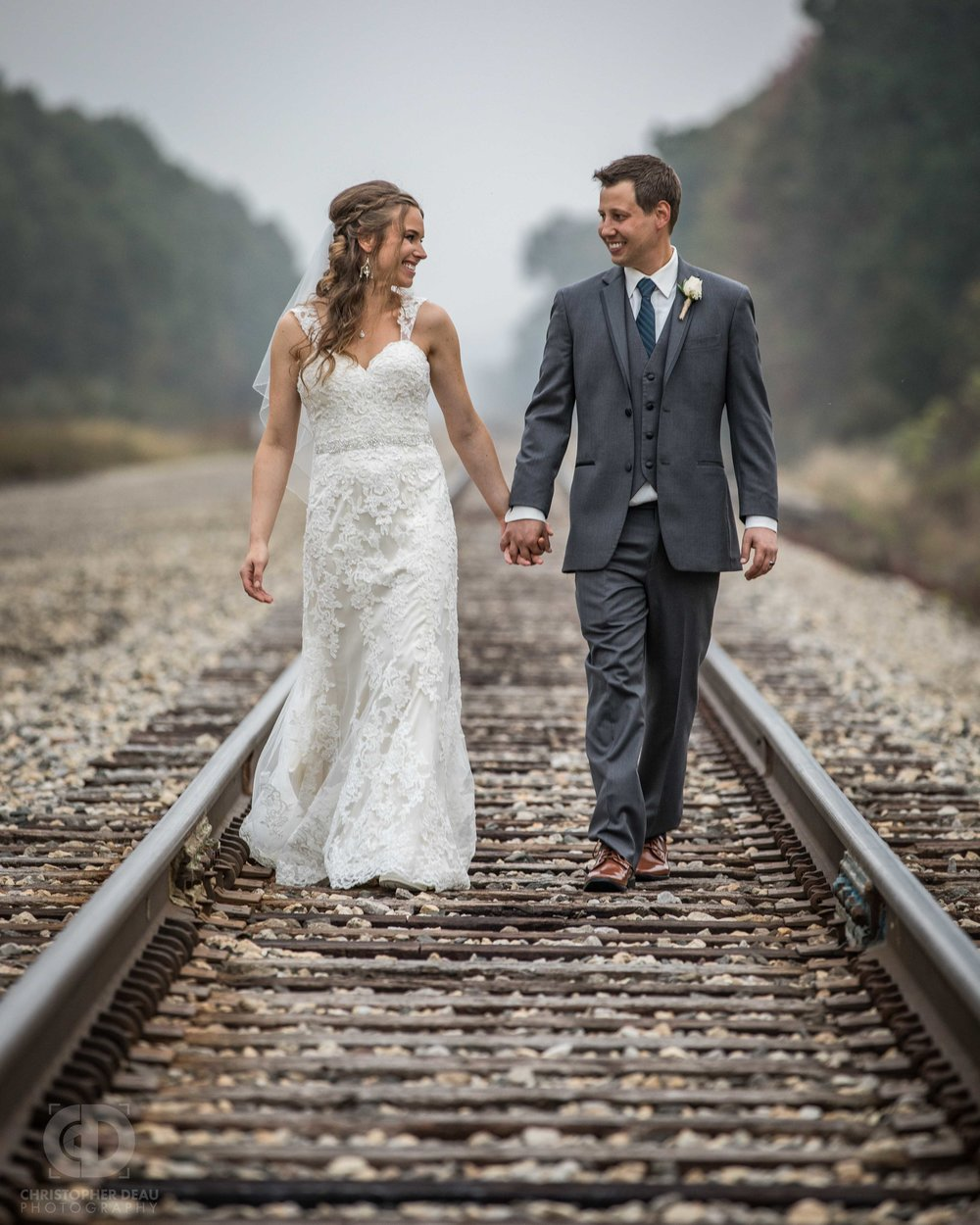 bride and groom walking down railroad tracks
