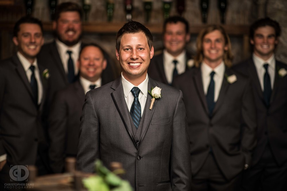 groom and groomsmen portraits in a wine cellar