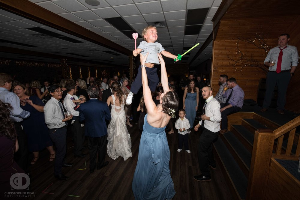 Bridesmaid throwing crying toddler into the air on the dance floor
