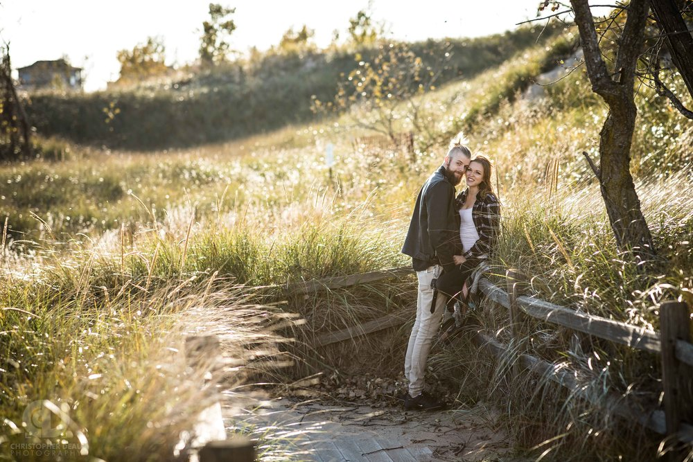 Dune grass preserve in Grand Haven, Michigan with couple leaning against a split rail fence