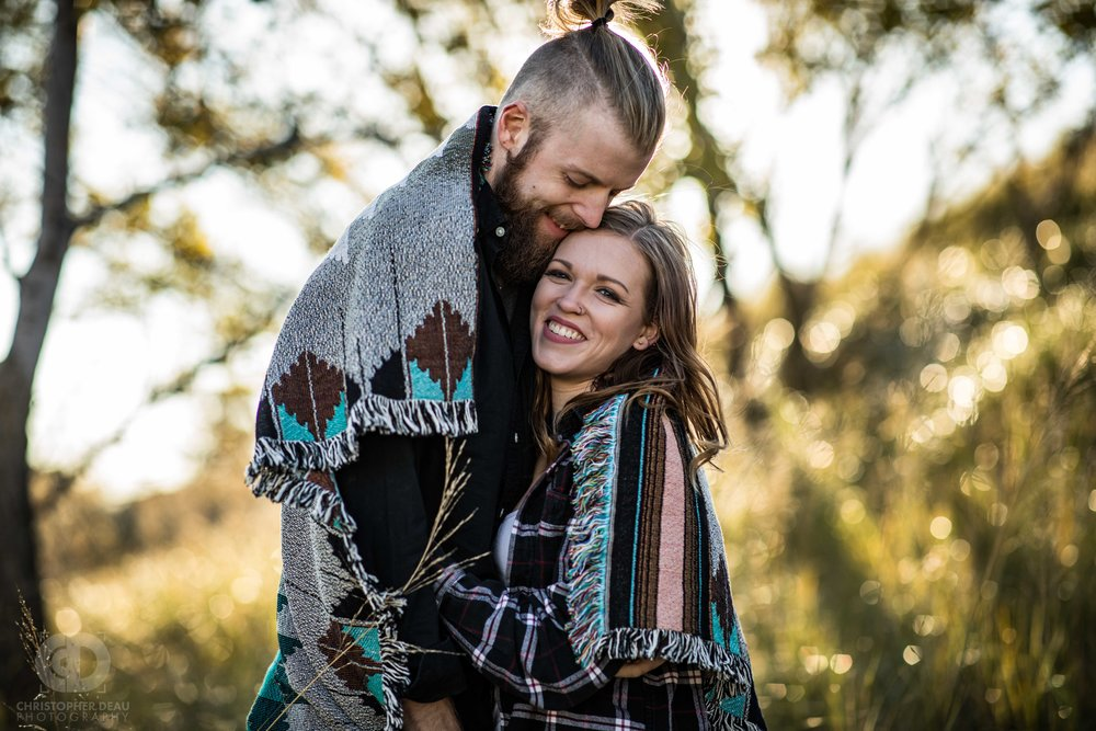 an engaged couple wrapped in a blanket surrounded by lake Michigan dune grass