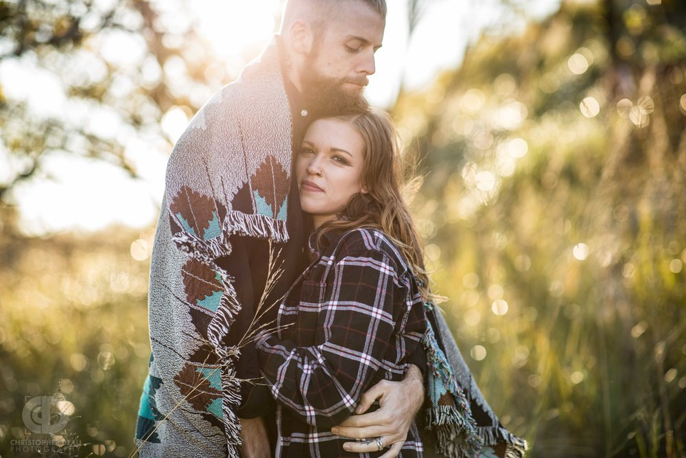 couple embrace, wrapped in blanket with sunset in background