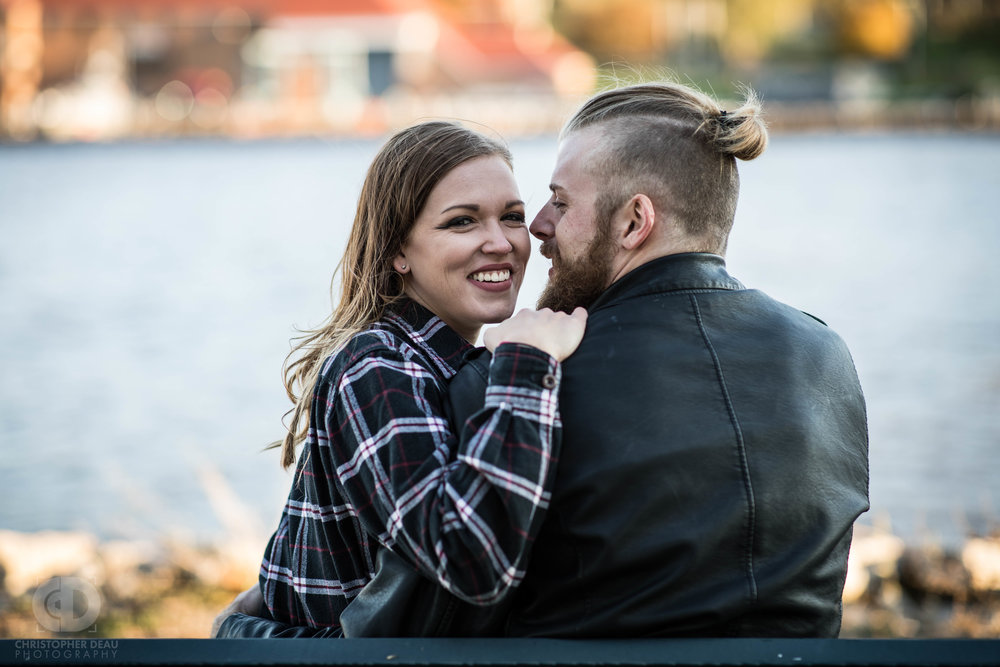 An engaged couple sits on a bench in front of the Grand River in Michigan