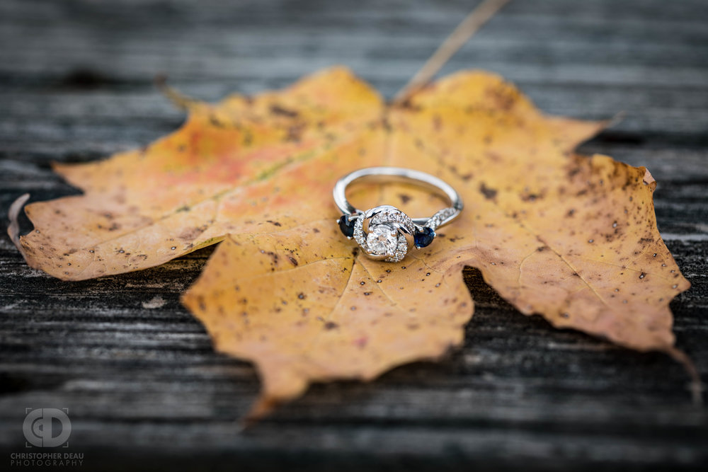 Fall engagement session photo of engagement ring placed on a fallen Autumn leaf sitting on a rustic barn wood table