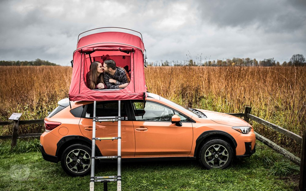 a couple takes their engagement photos in their Subaru Crosstrek roof tent while parked in an open tall grass prairie