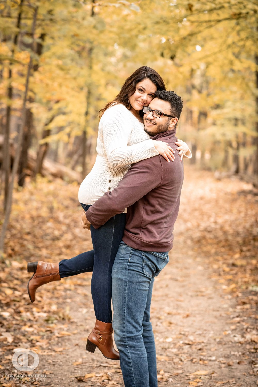 Man lifting woman for fall engagement photos