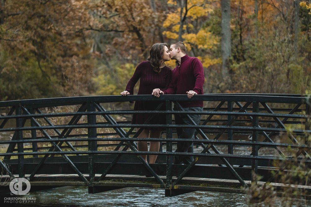 couple kissing on a bridge over a stream in Southwest Michigan