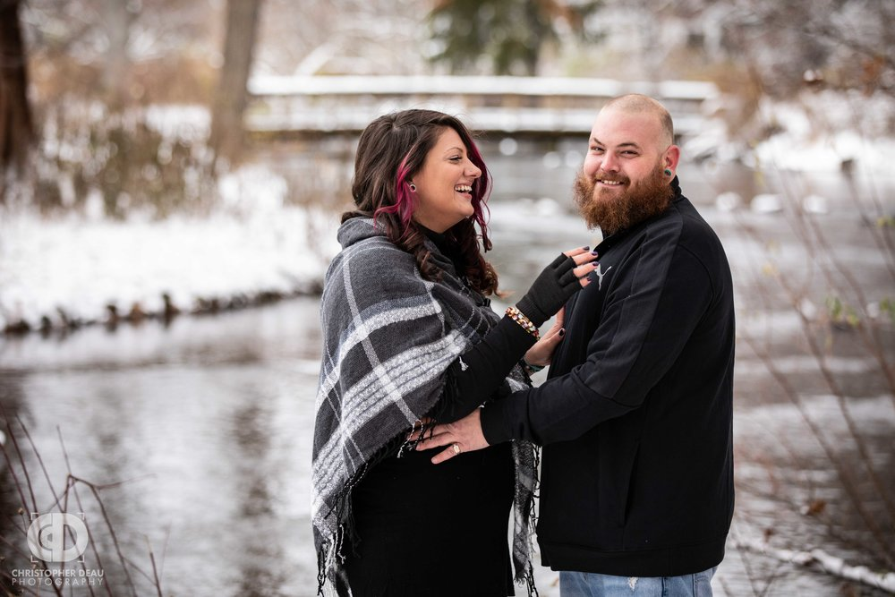 man and woman laughing in front of a stream and bridge in a southwest Michigan Park for their engagement photos