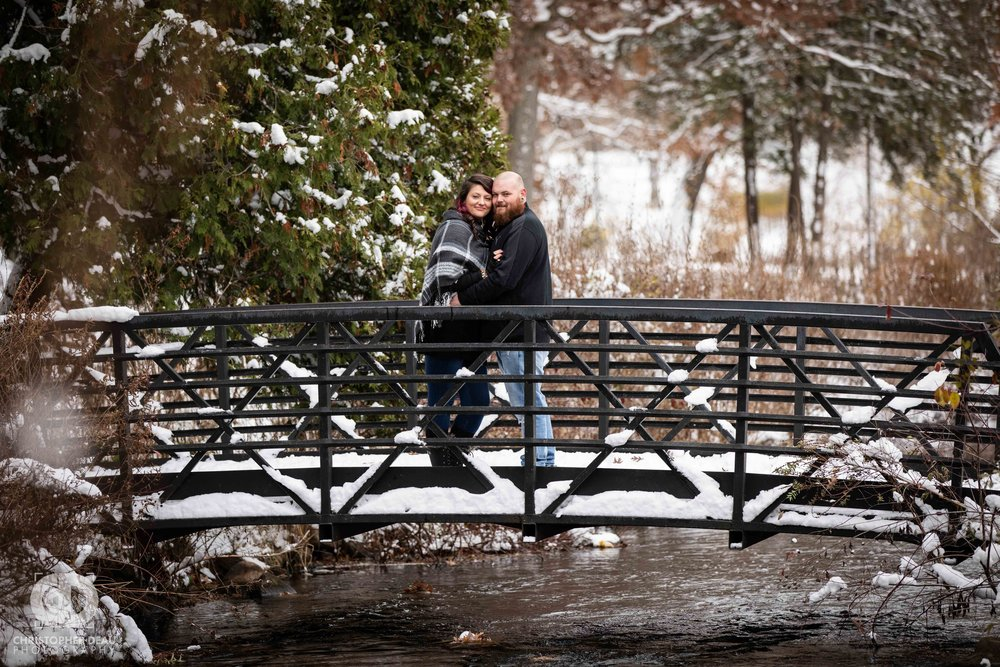 couple standing on a bridge over a stream at Milham Park in Kalamazoo