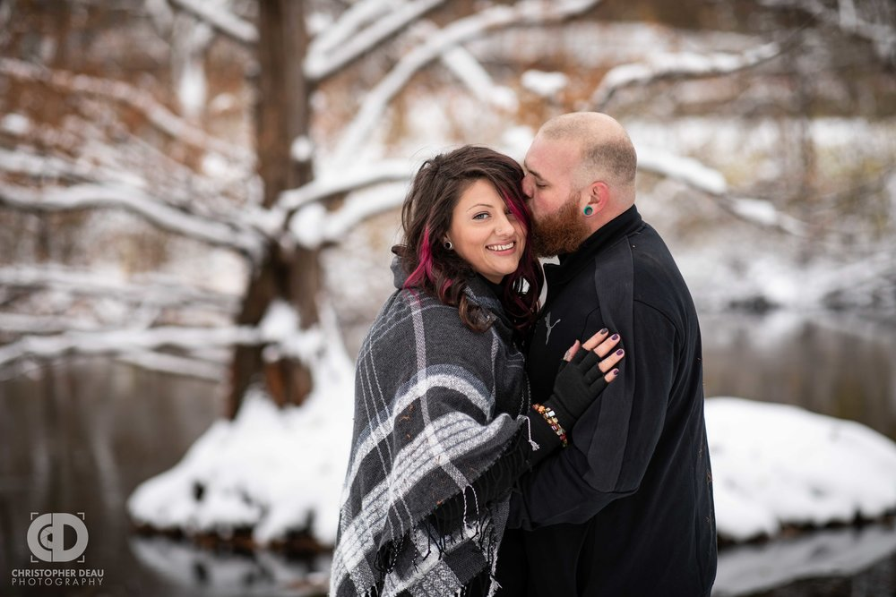 Man kisses a woman's head as she smiles at the camera with a stream and tree in background