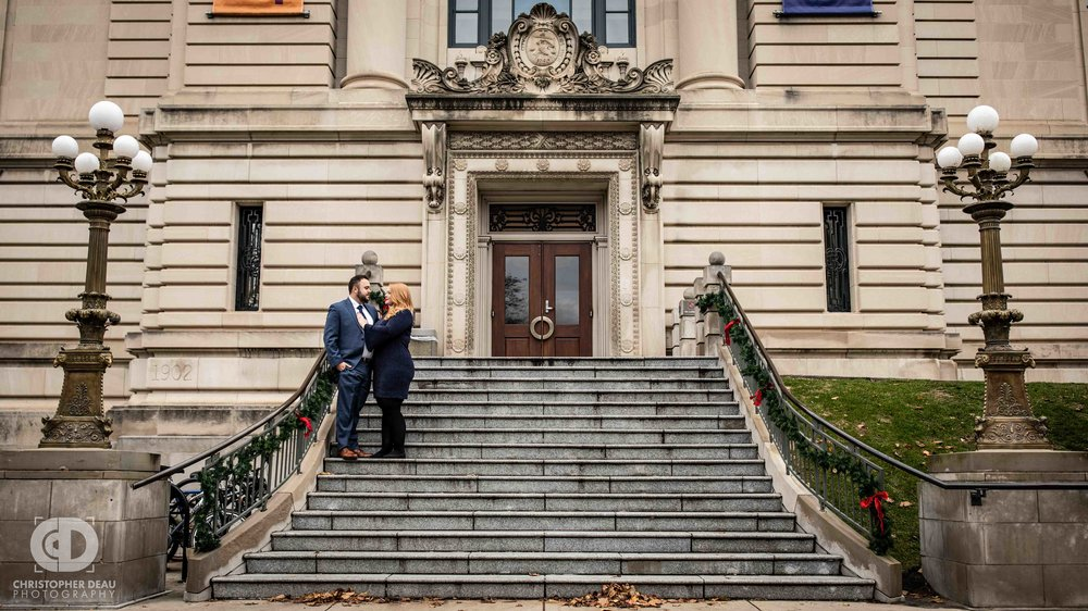 A couple poses on the steps of the Grand Rapids Public Library for their engagement photos